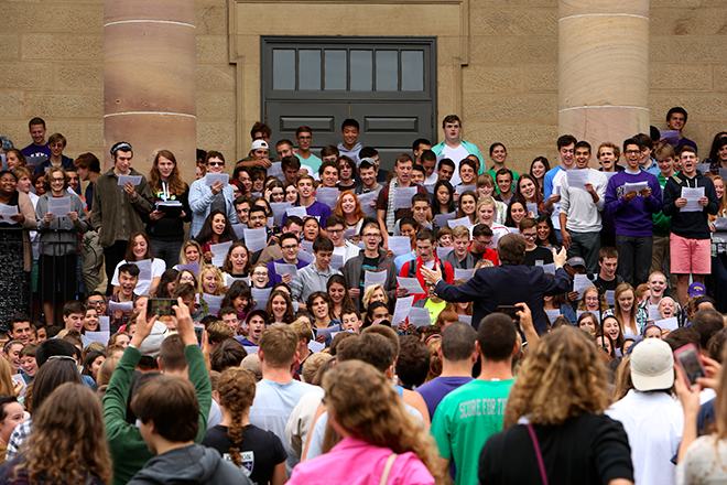 A large group of students sing on the steps of Rosse Hall.