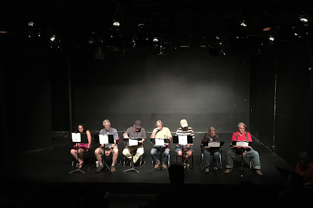 Several people sit on a dark stage performing a reading.