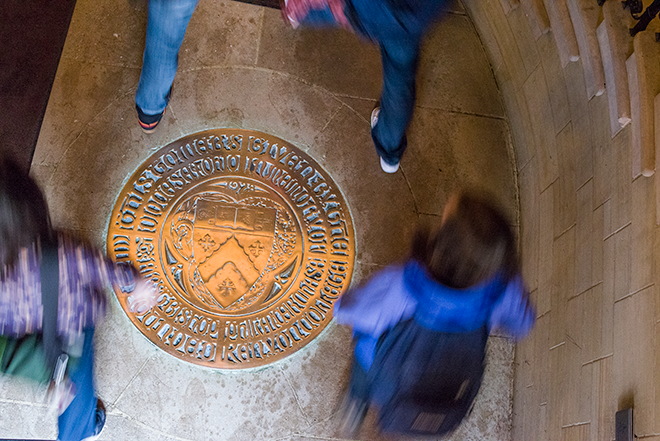 An overhead view of students stepping around a gold seal in Peirce Hall's floor.